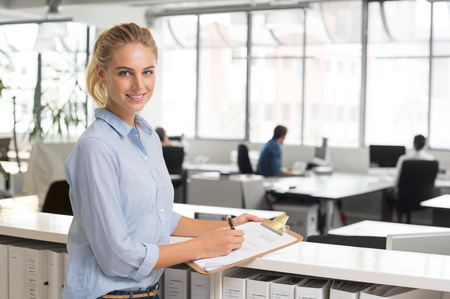 woman in office: Young cheerful business woman making notes in office. Portrait of happy young secretary smiling and looking at camera. Blonde businesswoman in office standing and writing on documents.