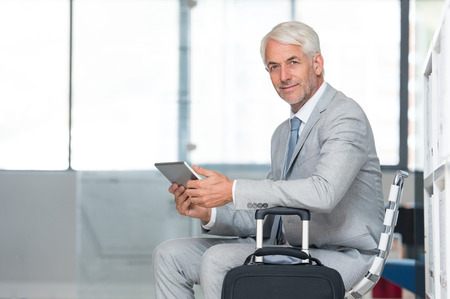 internet terminals: Happy successful businessman working on digital tablet while waiting at the airport lounge. Portrait of senior business man in formal checking mails on laptop and looking at camera