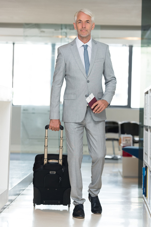 Senior business man carrying suitcase. Senior businessman walking with suitcase and holding flight ticket and passport in airport. Business traveler at international airport walking to terminal gate for airplane travel trip.