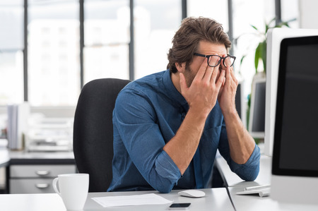 long hours: Portrait of an upset businessman at desk in office. Businessman being depressed by working in office. Young stressed business man feeling strain in eyes after working for long hours on computer. Stock Photo