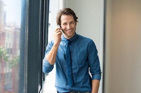persona feliz: hombre de negocios feliz en la oficina hablando por teléfono y mirando a la cámara. Sonriente hombre de negocios joven que tiene una conversación de negocios en el teléfono.