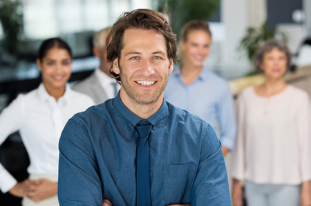 formals: Portrait of young businessman in formals standing with business team behind. Group of business people standing together in office. Young manager looking at camera in front of his team. Stock Photo