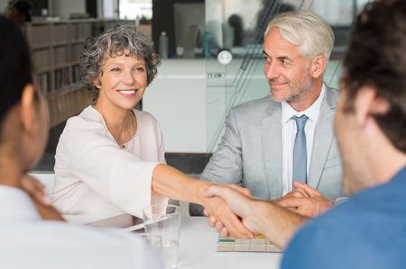 Schließen einer fröhlichen Senior Business-Frau auf Händeschütteln mit Geschäftsmann. Geschäftsleute, die Hände in Treffen schütteln. Handshake zwischen reifen Führung und jungen Geschäftsmann.