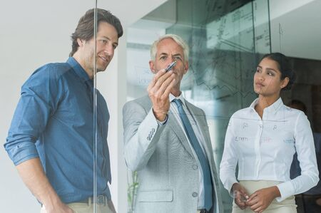 planning strategy: Business team planning a new strategy standing in front of glass wall drawing graph. Leaderhip thinking while drawing graph on glass in office. Business team discussing about growth with help of statistics during a meeting. Stock Photo