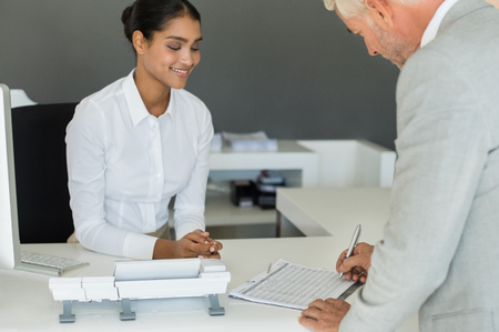 attendance: Senior businessman signing attendance sheet at reception desk. Cheerful receptionist asking senior business man to sign employee sheet. Senior businessman signed the attendance sheet. Stock Photo