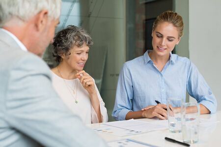 busineswoman: Senior businesswoman analyzing charts and graphs with her assistant and boss. Team of business people discussing during a meeting in a modern board room. Happy busineswoman reading report and thinking about future.