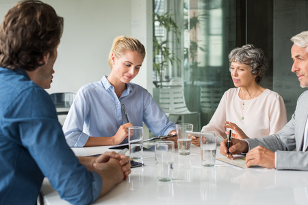 group strategy: Young businesswoman analyzing report with team. Group of marketing team discussion about new strategy in a modern conference room. Businessmen and senior businesswoman brainstorming for new marketing idea.