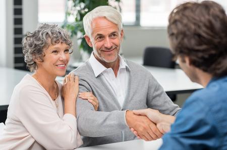 Gelukkig hoger paar handen schudden met pensioen consultant. Lachende senior man handen schudden met jonge zakenman voor zakelijke overeenkomst. Handdruk tussen senior man en financieel agent na het verkrijgen van een lening. Stockfoto
