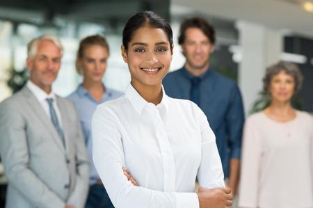 mujeres africanas: Empresaria multiétnica que se coloca con sus colegas en el fondo. Retrato de feliz sonriente mujer de negocios mirando a la cámara con el equipo detrás. El éxito de joven con los brazos cruzados en un entorno empresarial.