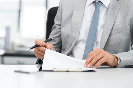 submission: Senior analyst managing business accounts. Close up of a senior businessman hands checking final report before submission. Close up of hands of leadership signing business contract.