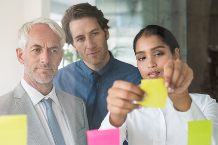 group strategy: Multi ethnic young businesswoman sticking adhesive notes on glass wall in office. Close up of leadership and his business team looking at sticky notes on window. Business teamwork during a meeting in a board room.