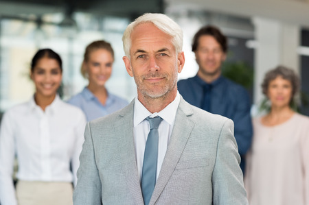 standing businessman: Successful mature businessman standing with businesspeople behind. Portrait of senior manager looking at camera in front of his business team. Happy smiling executive in suit.
