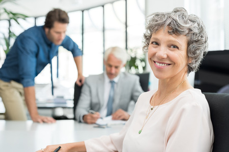executive woman: Close up face of executive businesswoman sitting in office while her team working in background. Portrait of smiling business woman sitting at desk and looking at camera. Happy senior woman satisfied with her company.