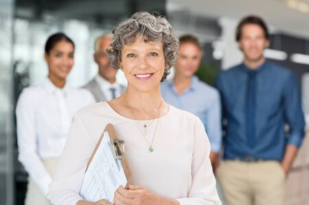 happy senior: Happy senior business woman standing with team holding document. Human resource manager looking at camera and holding progress report of employee. Happy senior businesswoman standing with business team in background.