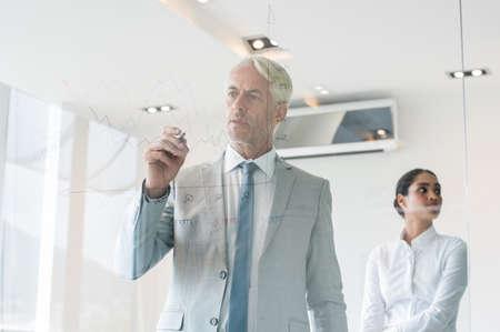 marker: Senior empresario de dibujo gráfico sobre la placa de cristal en la oficina. Jefe de la previsión de futuro de dibujo gráfico con su joven ayudante atrás. el liderazgo de pensamiento pensativo mientras que el dibujo estadística con el marcador en la pared de vidrio.