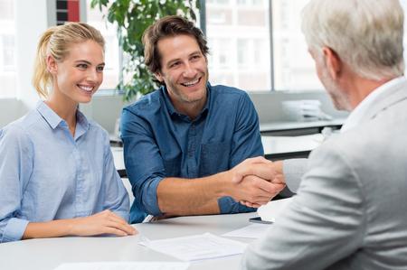 젊은 남자와 그의 여자 친구와 수석 금융 고문의 핸드 셰이크. 사업가 악수 계약을 서명하는 동안 몇 가지. 행복 한 미소 커플에 악수하는 부동산업자.