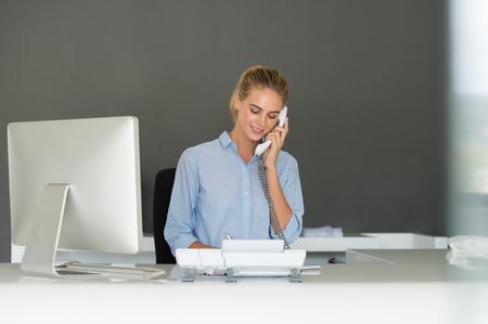 Recepcionista sonriente que usa el teléfono en el escritorio. El servicio al cliente de llamadas de teléfono de fabricación representativa. Hermosa mujer de negocios hablando por teléfono en el lugar de trabajo. secretaria joven hermosa que habla en el teléfono en la oficina. Foto de archivo
