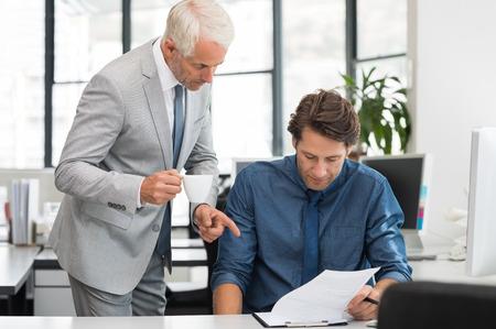 Älterer Geschäftsmann mit jungen Arbeitnehmer sprechen im Amt. Geschäftsleute, die mit Computer im Büro sitzen und Beratung. Senior Managing eine Tasse Kaffee auf Bericht Mitarbeiterführung zu halten.