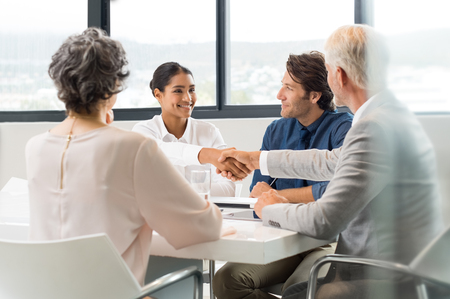 deal in: Handshake to seal a deal after a job recruitment meeting. Two successful business people shaking hands in front of their colleagues. Senior businessman shaking hands to young businesswoman in a modern office.