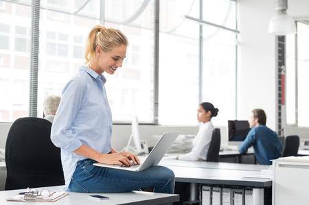 Lächelnde Geschäftsfrau sitzt auf dem Schreibtisch mit Laptop. Portrait der besetzten Sekretärin Typisierung in der Arbeitsumgebung. Glückliche junge Geschäftsfrau in der beiläufigen Arbeiten am Computer im Büro.