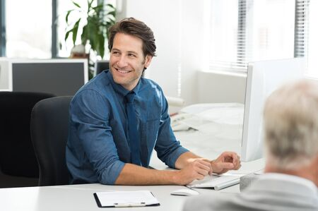 Cheerful young businessman working on desktop computer at office. Happy smiling business man looking away while working in office. Cheerful man sitting at desk in a co-work office. photo