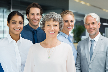 Successful group of business people at the office looking at camera. Senior woman standing with her business team in a modern office. Successful teamwork standing together. photo