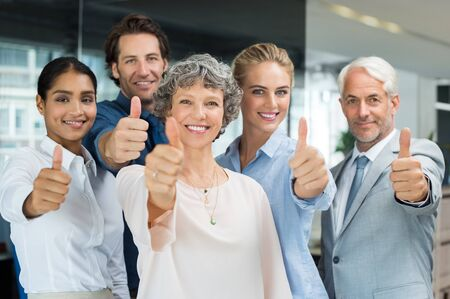 Group of happy business people showing thumbs up. Successful businessmen and businesswomen showing thumbs up sign and looking at camera. Portrait of satisfied business team cheering and showing thumbup at office. photo