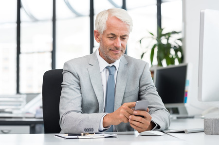 business man phone: Smiling senior businessman using mobile phone while working in office. Happy mature manager sending text message with smartphone. Senior business man typing on smart phone. Stock Photo