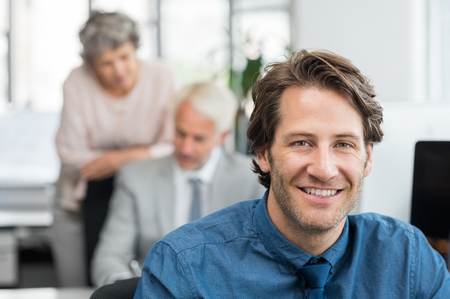 Close up face of handsome young businessman smiling in office. Portrait of a young broker sitting at office and looking at camera while financial experts working at computer at background. photo