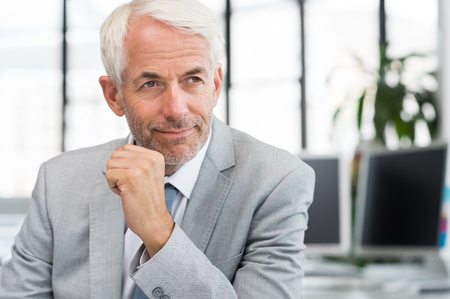 away: Portrait of a proud businessman in office thinking about a new plan. Portrait of mature businessman with hand near chin looking away. Close up face of a satisfied senior man sitting at a desk in office. Stock Photo