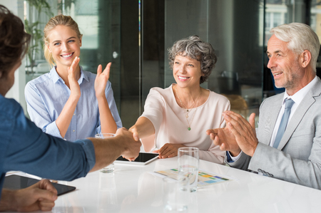 deal in: Handshake to seal a deal after a job recruitment meeting. Two successful businesspeople shaking hands in front of their colleagues. Mature businesswoman shaking hands to seal a deal. Stock Photo