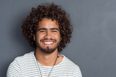 Portrait of a happy cheerful young man looking at camera. Handsome young man with beard and curly hair standing against grey background. Close up face of multi ethnic young man isolated against grey wall.