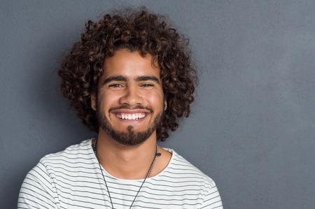 Portret van een gelukkig vrolijke jonge man op zoek naar camera. Knappe jonge man met baard en krullend haar staande tegen grijze achtergrond. Close-up gezicht van de multi-etnische jonge man geïsoleerd tegen de grijze muur.