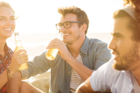 non alcoholic: Young man and woman drinking beer while sitting on beach at sunset. Group of guys and girls out on a picnic drinking non alcoholic drink. Smiling friends celebrating with beers summer vacation.