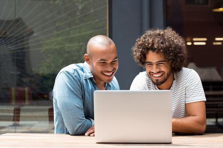 Twee gelukkige vrienden met behulp van laptop buiten. Gelukkige Afrikaanse jonge mannen lachen tijdens het kijken naar laptop scherm. Twee jonge lachende jongens met behulp van een laptop in een cafe bar.