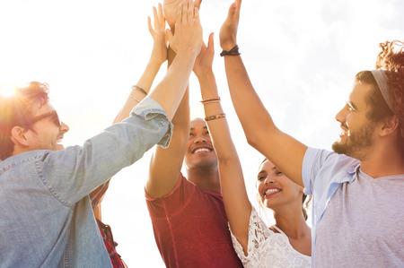 Groep gelukkige vrienden high five en plezier samen. Gemengd ras jongens en meisjes vieren succes. Vrolijke jonge mannen en vrouwen geeft high five aan elkaar.