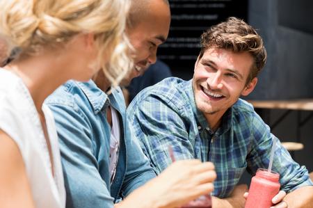 tomando leche: Grupo de amigos en un café de relax al aire libre. Retrato de hombre joven batido potable durante la conversación con los amigos en el café de la acera. Grupo de sonrisa de los individuos y de reunión niña feliz en la cafetería al aire libre.