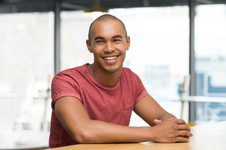 young man portrait: Young man thinking while sitting on the chair at cafeteria. Portrait of african guy in casual day dreaming. Cheerful young man smiling while looking away sitting on chair. Stock Photo