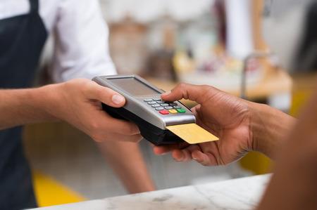 支払うクレジット カード スワイプ マシンを使用しての手のクローズ アップ。手が食堂で支払い端末からクレジット カードをスワイプします。男は