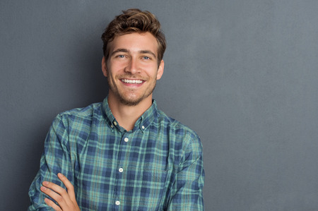 Junger stattlicher Mann lehnte sich gegen graue Wand mit verschränkten Armen. Fröhlich Mann lachend und in die Kamera mit einem großen Grinsen suchen. Portrait eines glücklichen jungen Mann, der mit verschränkten Armen auf grauem Hintergrund.