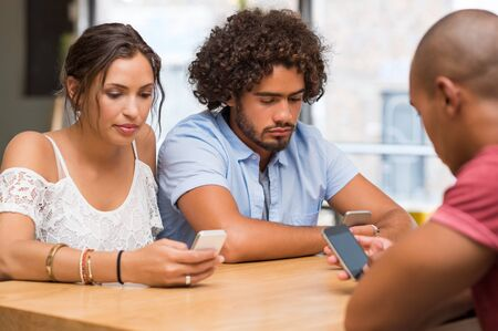 ignoring: Group of friends sitting in cafe separately looking at their phone losing communication. Young men and girl playing with smartphones and ignoring each other. Young people looking down at cellular phone.
