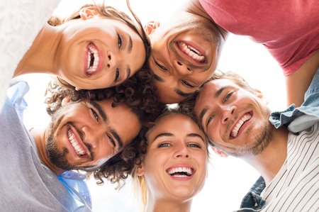 directly below: Directly below shot of young friends forming huddle. Low angle view of girls and guys with their head forming a circle. Portrait of young people looking at camera. Friendship and unity concept. Stock Photo