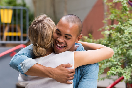 outdoor outside: Happy smiling african man hugging young woman outside cafe. Attractive young couple hugging each other and smiling. Happy friends laughing and hugging outdoor.