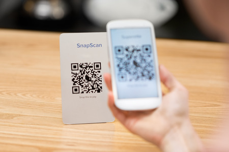 Closeup of a hand holding phone and scanning qr code. Woman hand paying with qr code. Close up of customer hand making payment through smart phone and scan code. Reklamní fotografie - 59968168