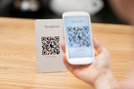Primer plano de un código QR teléfono explotación de la mano y escaneo. Mano de la mujer que paga con código QR. Cerca de la mano del cliente de hacer el pago a través de teléfonos inteligentes y el código de exploración.