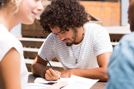 hombre escribiendo: Cierre plano de un hombre joven que estudia con los amigos. Retrato de un estudiante con la barba y el pelo rizado preparación para examen de la universidad con los amigos. Enfocados jóvenes escribir notas en el cuaderno hombre.