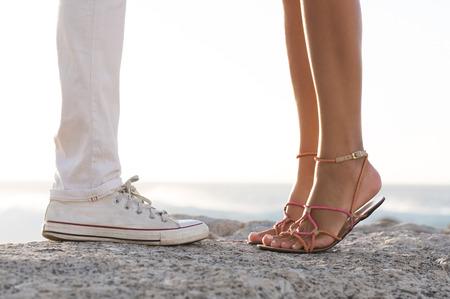 Close up der Beine eines Paares auf dem Meer auf einem Felsen zu küssen. Nahaufnahme der Füße des jungen Mannes und der Frau auf in der Liebe bei einem romantischen Datum tiptoed. Junges Paar in der Liebe am Strand. Standard-Bild