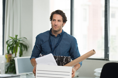 layoff: Portrait of fired businessman holding box with documents in office. Portrait of a young businessman carrying box at his workplace. Layoff concept.