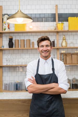 腕を組んでコーヒー ショップのカウンターで傾いている笑顔若いウェイターの肖像画。カメラ目線エプロンと成功の所有者。若者をキッチンに立っ