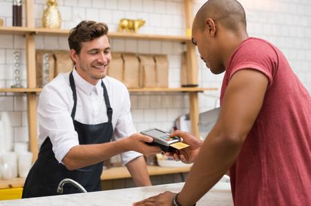 Camarero que sostiene la máquina golpe de tarjeta de crédito, mientras que el código escribiendo al cliente. África joven haciendo el pago en la cafetería con tarjeta de crédito. Cliente que paga por el café y el almuerzo por el lector de tarjetas de crédito.